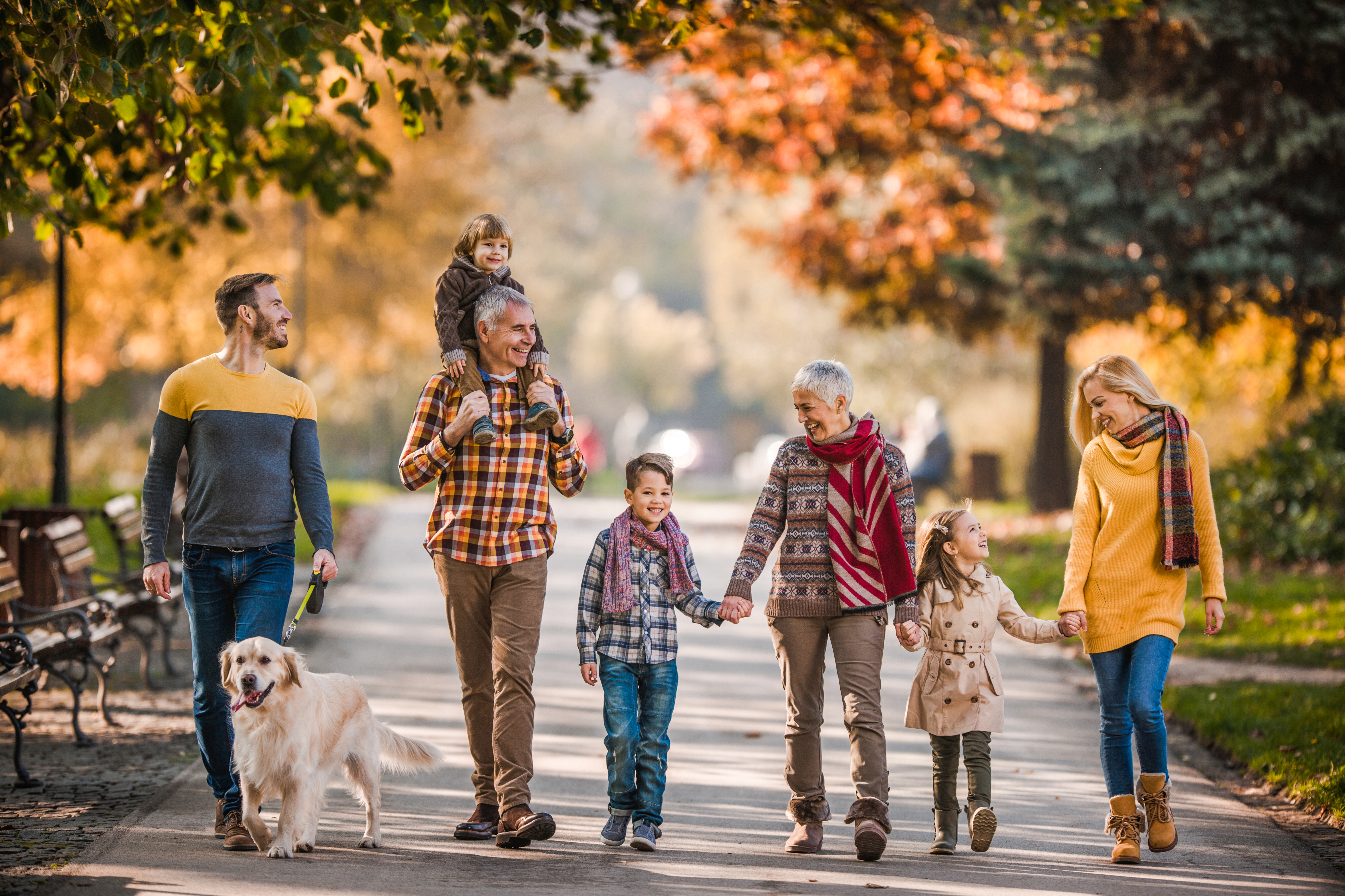 Happy  extended family walking their dog and communicating in autumn day at the park.
