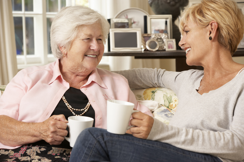 Adult Daughter Visiting Senior Mother Sitting On Sofa At Home Having A Chat Whilst Drinking Tea